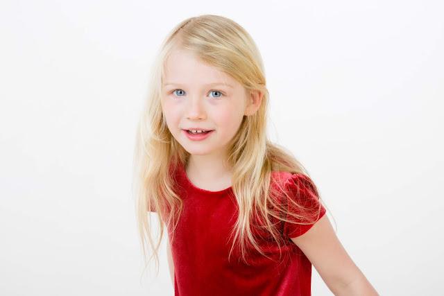 A long blonde haired girl in a red velvet dress
