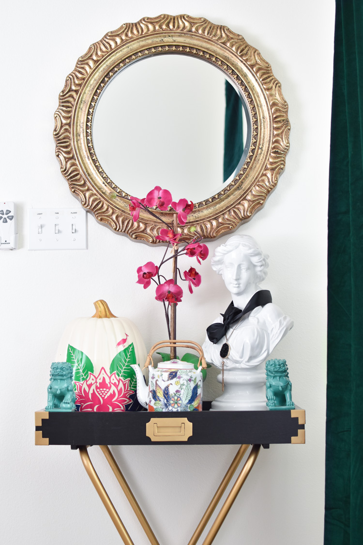Tobacco leaf pumpkin and teapot sit on a campaign style butler stand in a dining room with chinoiserie decor and white walls.