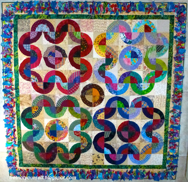 Thirty-six bullseye blocks are arranged by color into four 'flower petal' shapes on a quilt with a Texas Mink fringe border.