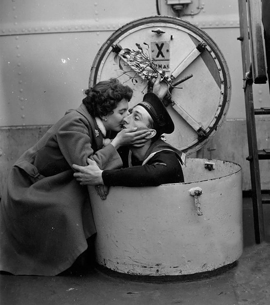 60 + 1 Heart-Warming Historical Pictures That Illustrate Love During War - D. Brown Kissing Her Fiance Terry Under The Mistletoe, On Board The HMS Wakeful At Portsmout, 1955