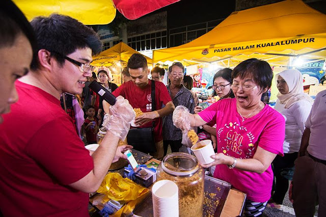 Customers like this happy Auntie having a good time scooping and stacking up her favourite cup of Oloiya Meat Floss at one of the night market!