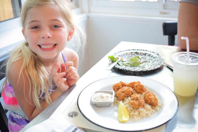 Little girl enjoying shrimp and rice at Gilbert's Underground Kitchen in Fernandina