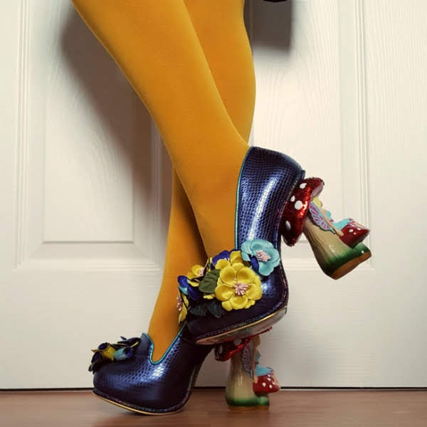 bent leg wearing mustard tights and blue metallic shoe with fairy toadstool heel