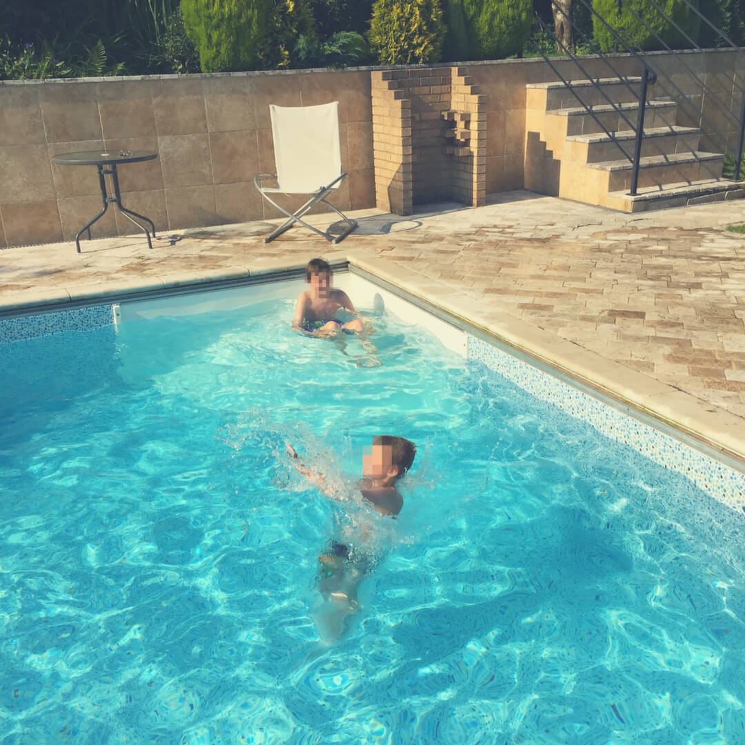 Boys play in a swimming pool in the sun.