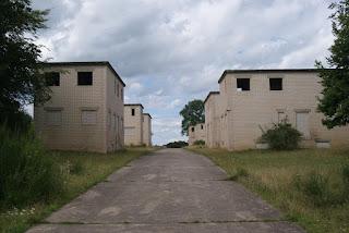 Quadratische, weiße Gebäude ohne Fenster. Inmitten ein asphaltierter Weg