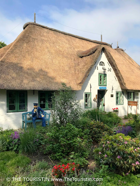 The sculpture of a seaman sitting on a blue bench in front of a white cottage with a thatched roof in the midst of a cottage garden..