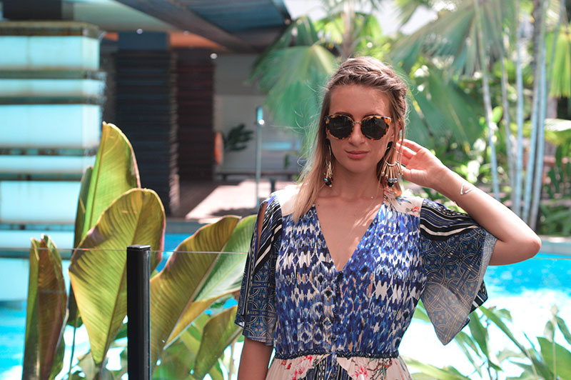 blonde fashion blogger wearing printed dress with tory burch brown sunglasses statement boho earrings