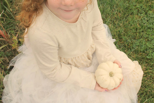 Red haired child holding baby boo white pumpkin - Hello Lovely Studio