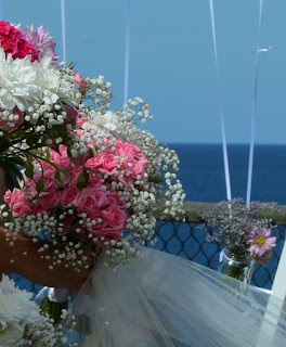 bunch of wedding pink and white wedding flowers, a handful of tulle, a posy in a jam jar with the Pacific Ocean in the distance.