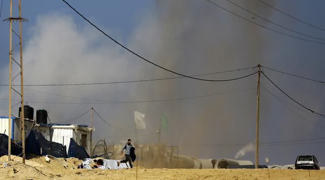 Seorang pria berlari menyelamatkan diri dari gempuran serangan udara Israel di Jalur Gaza Utara, Senin (6/2). (AFP PHOTO / MOHAMMED ABED)