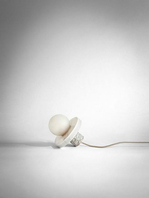 Eine weiße Lampe aus Marmor, Granit und Glas liegt auf einem weißen Boden