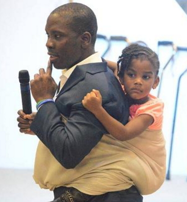 nigerian pastor carries baby back preaching