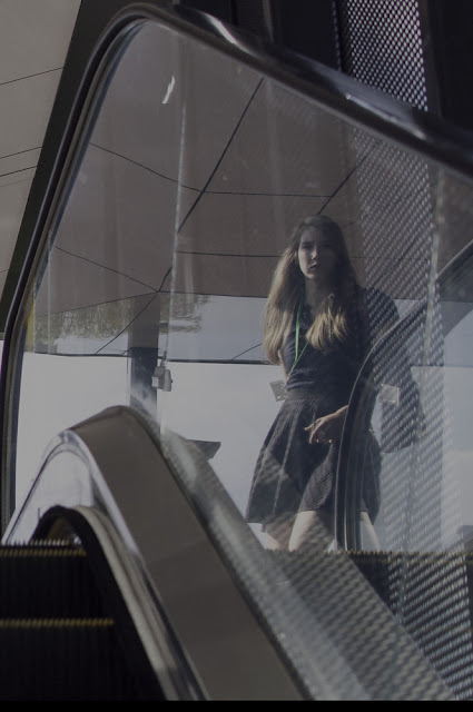 Photo showing upwards escalator with a young lady reflected off the glass side