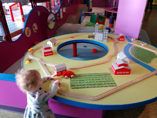 toddler with curly hair playing with train table in the toddler zone of LaunchPad Children's Museum in Sioux City, Iowa