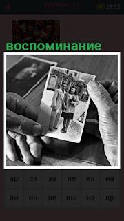 в руках черно белые фото, по которым происходит воспоминание