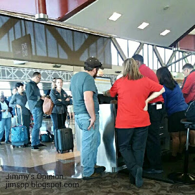 Line of people at an airline counter with our son Tim looking on to the airlines computer while an agent searches for a flight.