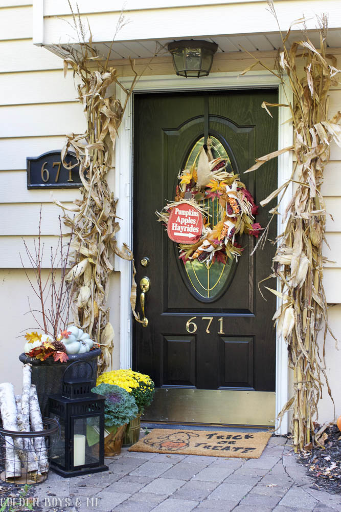 Front door fall decor with corn stalks and wreath