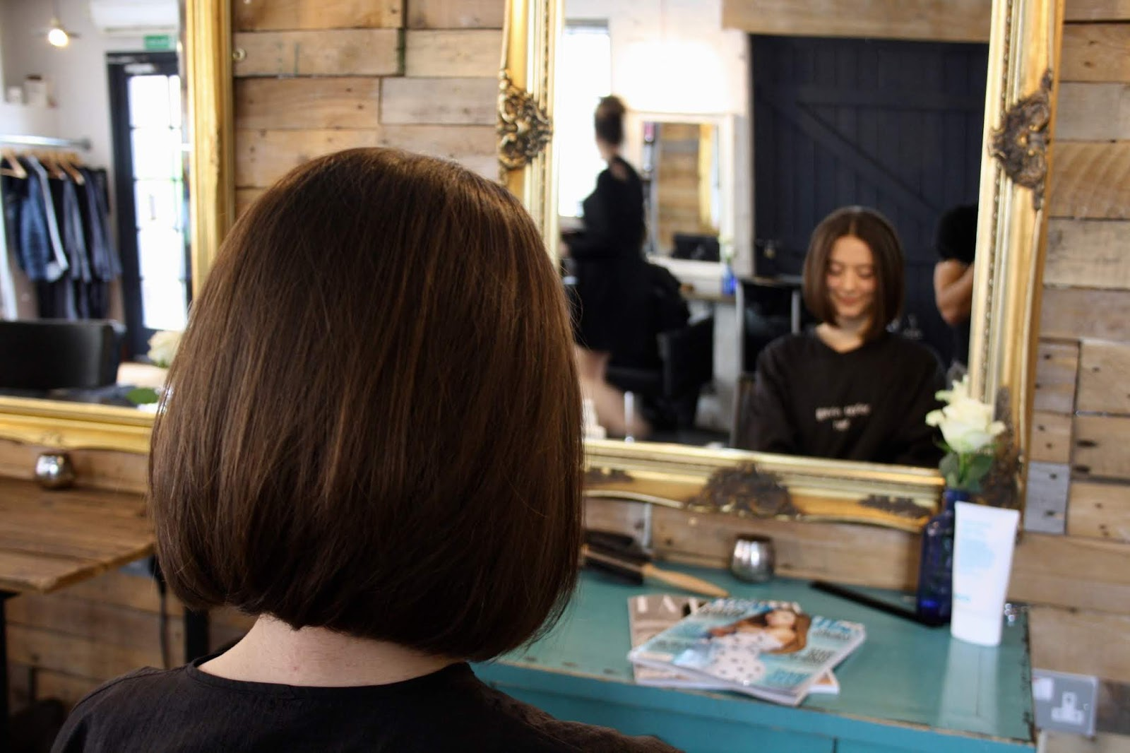 Abbey, with a sleek brunette haircut, sits facing a gold mirror in the Gavin Taylor Hair salon