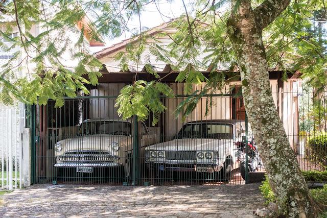 Duas casas de madeira e dois carrões