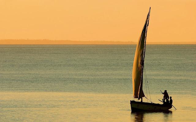 Foto met een boot op zee bij zonsondergang