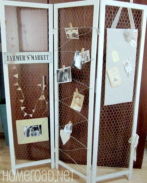Chicken wire room divider with bulletin board, photos and signs hung on it.