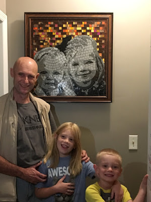 Fred the mosaicist and Ella and Lane standing under their mosaic portrait