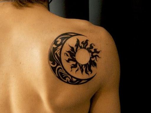Esta inspiração tribal tatuagem, retratado em tinta preta, mostra uma lua crescente, envolvendo em torno de um sol sobre o utente direito ombro.