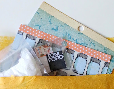 Selection of small scrapbooking paper pages, miniature books and a wrapped parcel peeking out of a bubble bag.