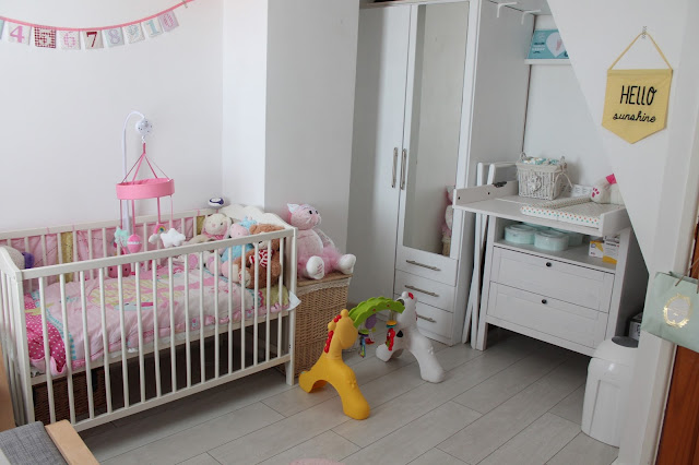 baby girl bedroom with white wooden floor and furniture and number bunting on wall