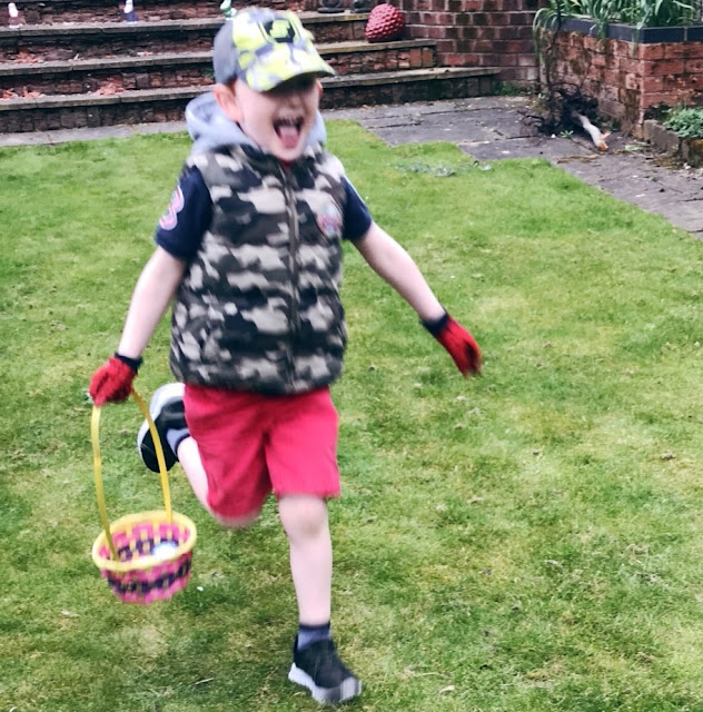 Little boy running with an Easter basket containing Easter eggs