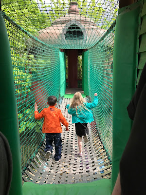 two children running across a high up walk way surrounded by netting