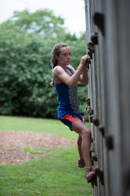 teenage girl climbing a rock wall