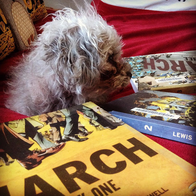 Murchie lies on a red blanket, all three volumes of the March Trilogy arranged in a fan around him. The book closest to the viewer has a yellow cover with a slew of suited men's feet marching along across the top. The other two books are less visible, but the second one gives the impression of a bus in flames and the furthest volume shows people marching across a bridge with the book's title emblazoned on its ashphalt.