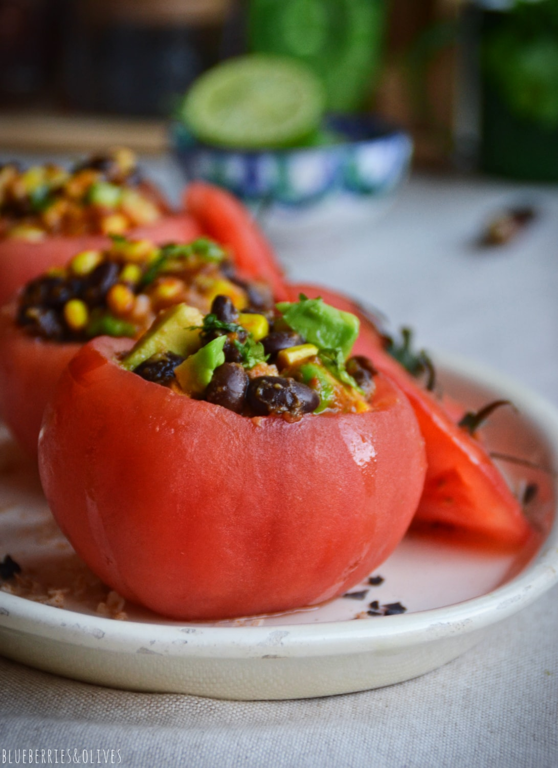 STUFFED TOMATOES IN WHITE PORCELAIN DISH, CILANTRO LEAVES,INGREDIENTS IN BACKGROUND