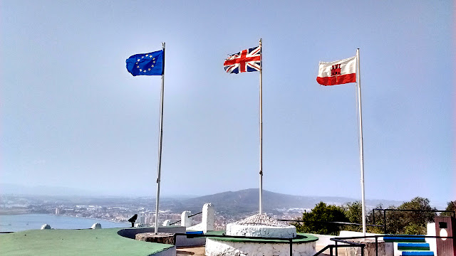 Photo of the European Union (EU), United Kingdom (UK), and Gibraltar flags flying side by side. Gibraltar is the only British territory that's also part of the EU.