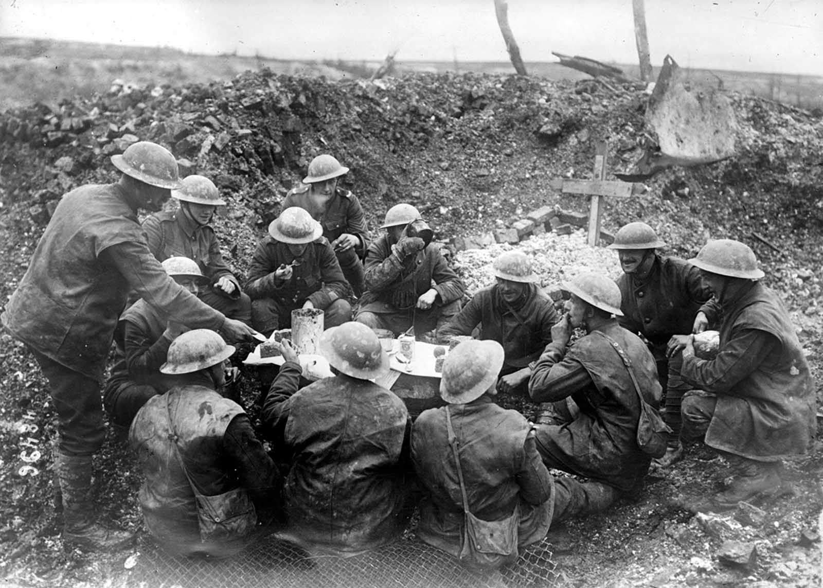 On the British front, Christmas Dinner, 1916, in a shell hole beside a grave.