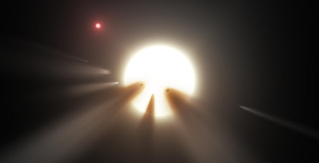 This artist's conception shows a star behind a shattered comet. One of the theories for KIC 8462852's unusual dimming is the presence of debris from a collision or breakup of a planet or comet in the star's system, creating a short-term cloud that blocks some starlight. Image is courtesy of NASA/JPL-Caltech.