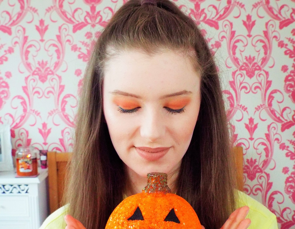 Looking down toward pumpkin in hands, showing long delicate lashes