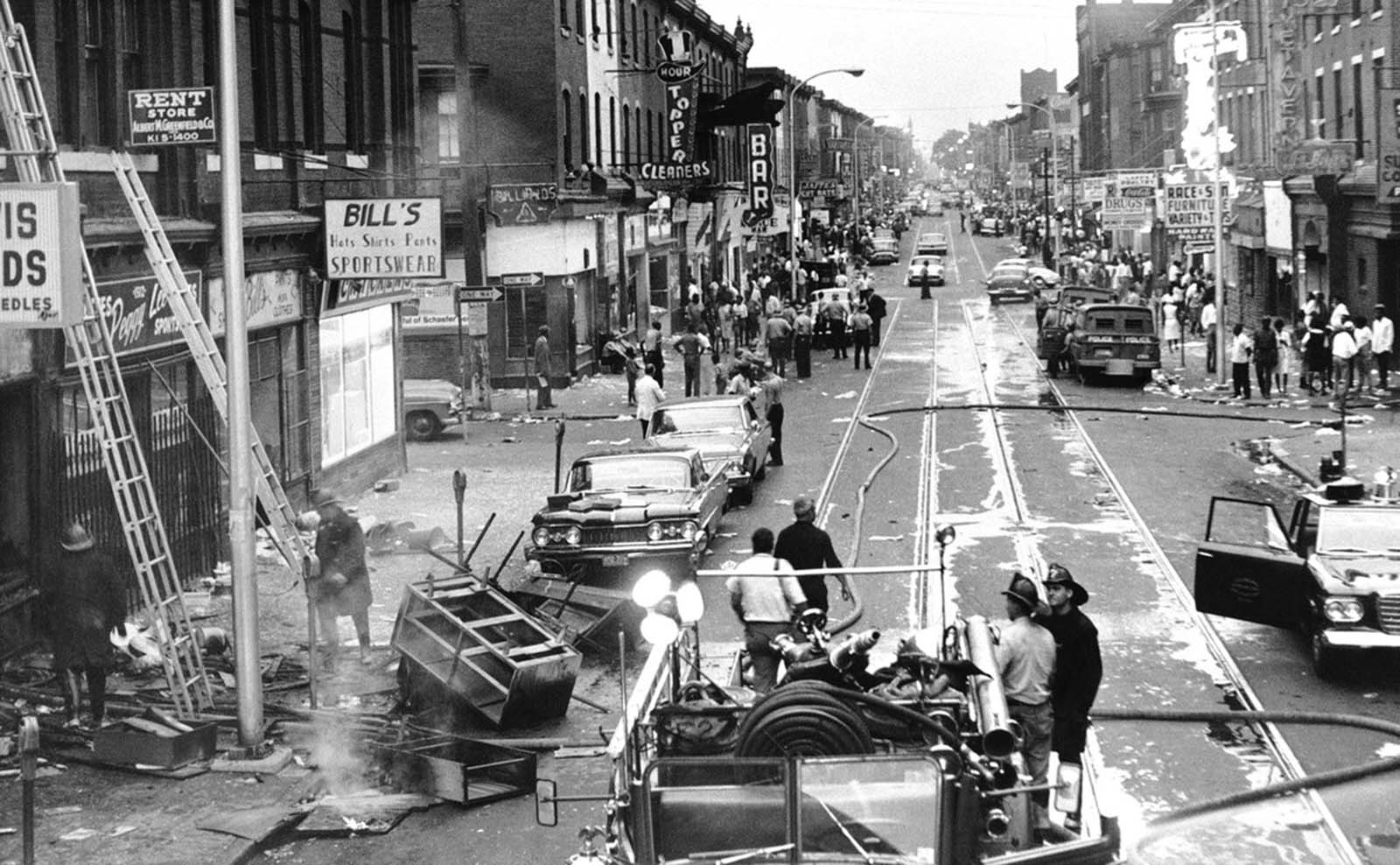 This view looking west from 15th Street on Columbia Ave. shows Main Street was involved in rioting in the predominantly black area of North Philadelphia during the previous night and continuing into August 29, 1964. At left, firemen clear smoldering rubble from wrecked store. Demonstrators, bystanders and police line street in background. Looting was widespread and damage heavy. At least 50 persons were injured including 27 policemen.