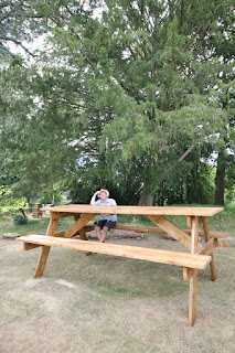 Luke Jerram sits casually dressed on an over-sized picnic bench in the Botanic Garden