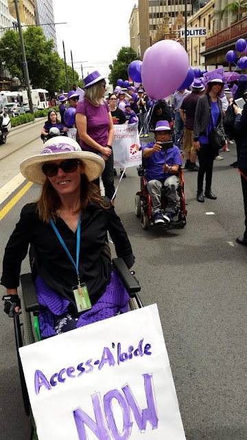 Jodie is in the foreground with the parade behind her. The placard is balancing on her feed and against her knees. She is wearing a black shirt. The purple cardigan has been shrugged off  and has settled around her waist. Behind are balloons and people walking and with gophers and chairs.