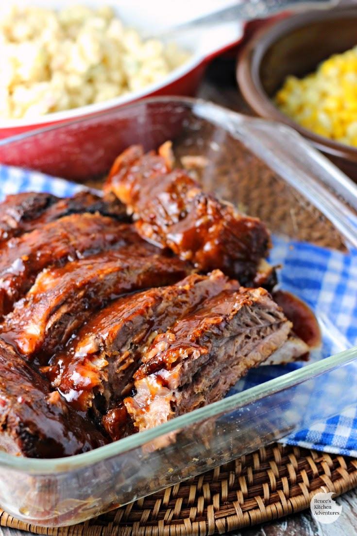 Fall-Off-The-Bone Slow Cooker Ribs by Renee's Kitchen Adventures ready to serve in clear serving dish with sides in the background