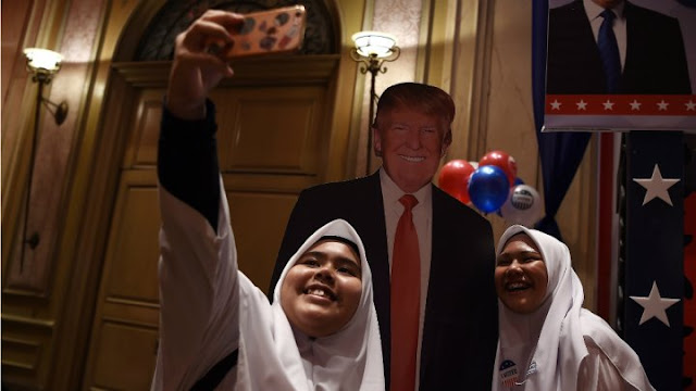 Malaysian Muslim school girls pose for a selfie with a cut-out of the US presidential candidate Donald Trump during an event to follow the election results in Kuala Lumpur on November 9, 2016.