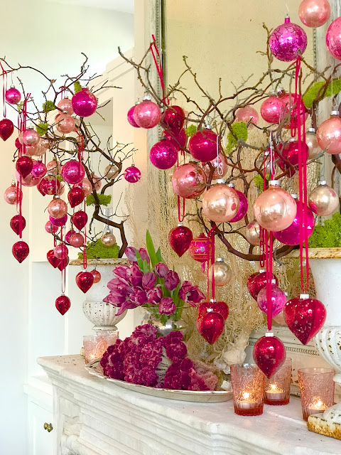 Valentine's Day Mantle Decor; heart ornaments, pink antique ornaments, pink tulips, pink flowers, antique mirror, limestone mantle