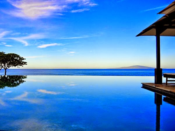 blue infinity pool blends into blue sea in paradise