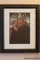 Photograph of a framed and matted photo of a couple hanging on the wall by Cramer Imaging