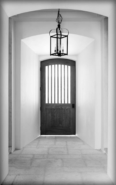 black front door white walls foyer entryway entry iron lantern