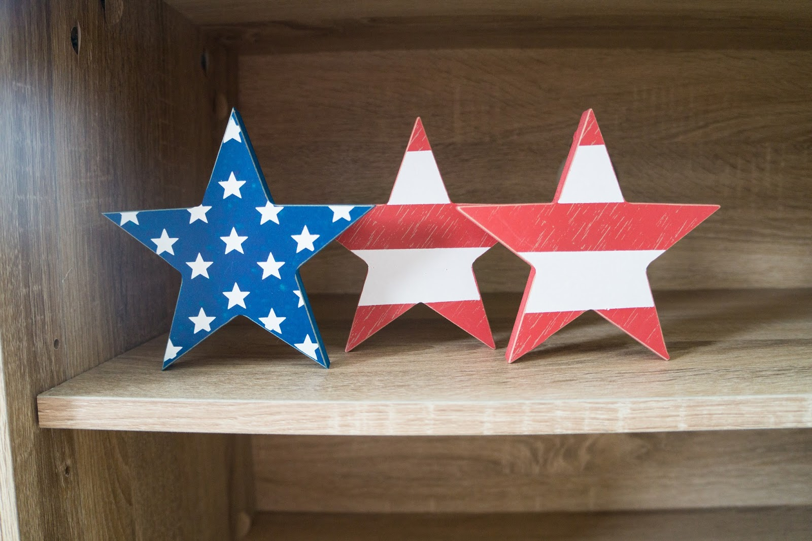 Three pieces of star shaped wood with an American flag design.