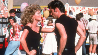 Fotograma de Grease con la pareja protagonista, uno frente a otro, bailando al ritmo de la canción You're the One That I Want