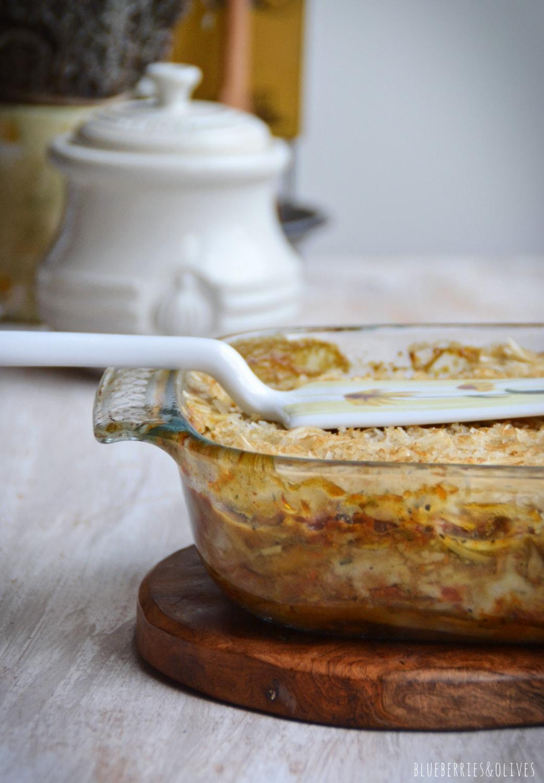 Lasaña de berenjenas en fuente de cristal sobre tabla de madera, con ingredientes de fondo, hierbas aromáticas, laurel seco, molinillo pimienta, espátula vintage para servir